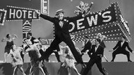 Schwarz-weiß: Gene Kelly bei Tanzszene in dem Film 'I'm singin' in the rain'.