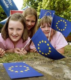 Mädchen mit EU-Fähnchen liegen auf Wiese.; Rechte: imago